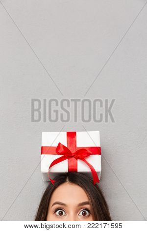 Funny image of cool woman bulging her eyes and posing with bithday present with red bow on her head, isolated posing over gray background