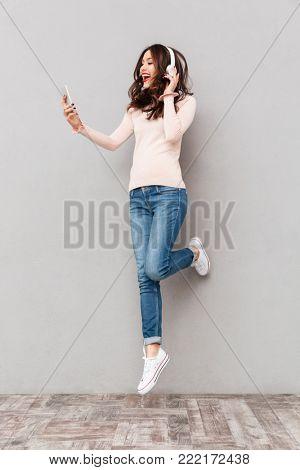 Full-length amazing female music lover wearing white headphones, taking pleasure in listening to music in smartphone over gray background