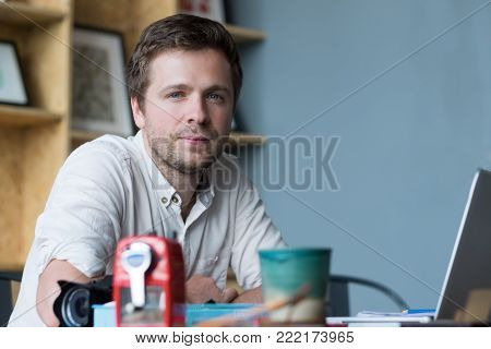Close up portrait of cheerful middle aged caucasian man sitting at his desk in office. Concept of positive work space