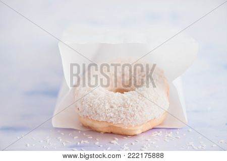 Close-up of a white donut with coconut topping on a light background inside paper delivery packaging. High key food photography.