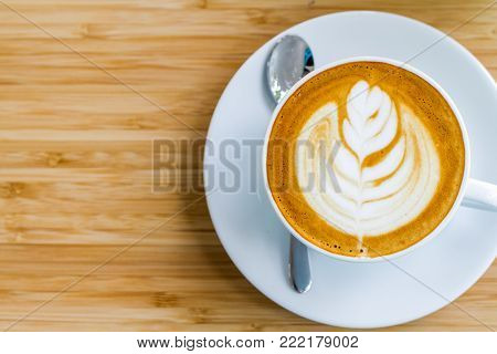 Hot coffee latte with latte art on wooden table