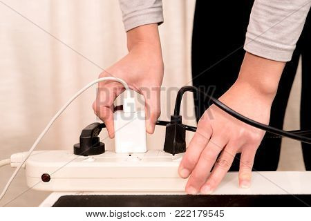women hand putting the electric plug on the electricity supply connection
