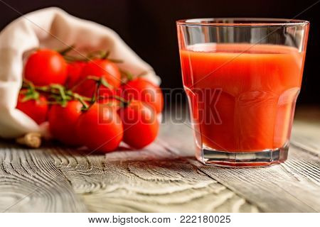 Two glasses of tomato juice with fresh tomatoes and herbs on rustic wooden background. Selective focus