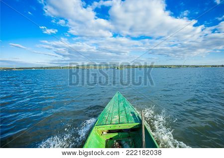 Old boat with oar near river or beautiful lake. Calm sunset on the nature. Fishing boat reflections in water romantic lagoon landscape