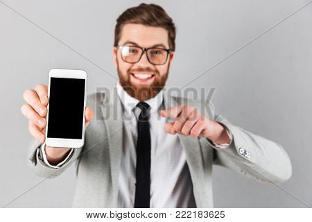 Close up portrait of a happy businessman dressed in suit and eyeglasses pointing finger at blank screen mobile phone while standing and looking at camera isolated over gray background