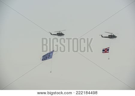 Pattaya, Thailand - November 20, 2017: Two helicopters  flying with Thai Navi flag and IFR2017 flag on misty sky on the 50th anniversary ASEAN international fleet review 2017 in Pattaya, Thailand