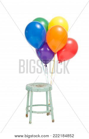 Six helium balloons each a different color of the rainbow are tied to a stool with no one. Simple birthday set up. Isolated on white.