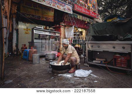 Man kneads dough in the street Delhi. India. 27.11.2017.
