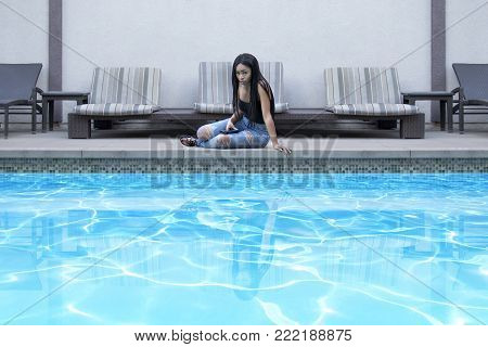Sad lonely black female waiting by the hotel pool looking depressed.  She is waiting by the resort swimming pool.  The image depicts depression when traveling solo or being heartbroken.