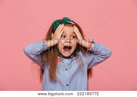 Thrilled little girl reacting emotionally grabbing head with both hands being shocked, screaming over pink background poster