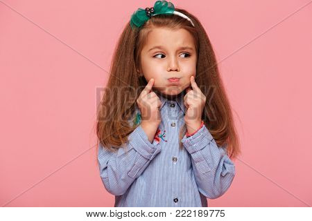 Caucasian sweet little girl 5-6 years with beautiful long auburn hair blowing up her cheeks, touching face over pink background