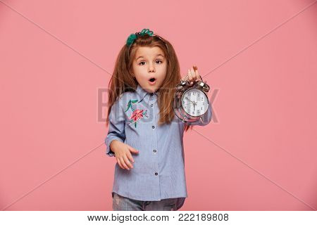 Shot of female kid posing on camera with eyes and mouth wide open, holding clock nearly 6 being shocked or shaken up over pink background