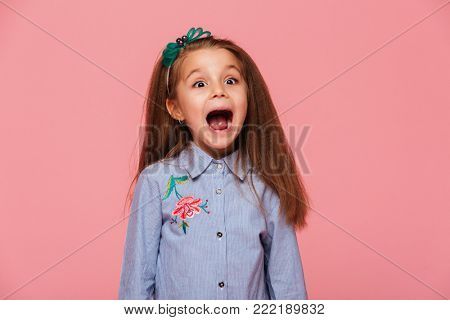Joyous female kid in trendy shirt having fun shouting, being excited and emotional over pink background