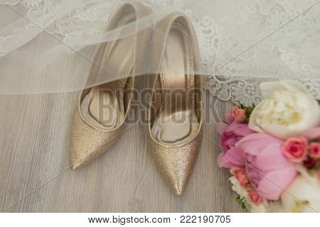 Golden bridal shoes are covered with a veil. Wedding details.