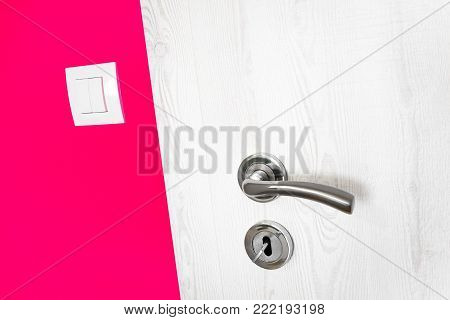 White wooden door with metal handle and keyhole with key in a bright vivid raspberry red wall in a modern house with a small electricity light switch in a close up diagonal view