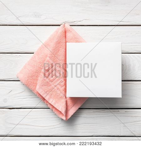 White box mockup next to pink towel. Top view.