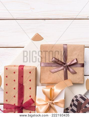 Gift boxes on white wooden desk top, top view