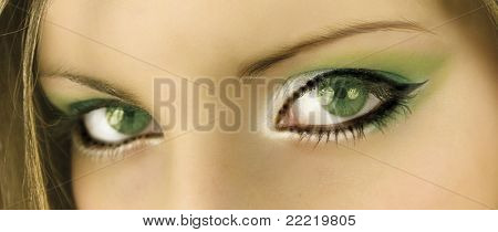 green eyes of a woman with green make up