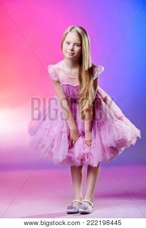 Fashion concept. Portrait of a pretty nine year old girl in an elegant fluffy dress. Kid's fashion.