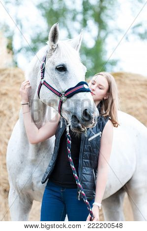 Portrait of pretty young blondy teenage cheerful girl owner with her favorite white horse at farm yard on yellow hay/straw rolled stack background. Vibrant colored outdoors vertical summertime image.
