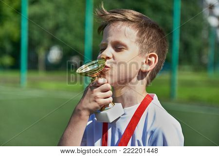 Winner Boy Football Player With Cup And Medal