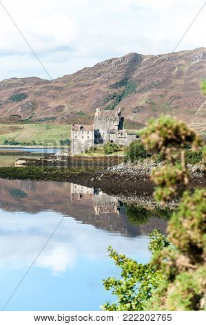 Majestic castle at Eilean Donan reflected in the high tide on Loch Alsh with sunny mountains and blue sky on background. Summertime outdoors vertical image.