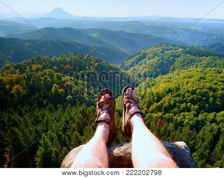 Long tired naked legs in hiking sandals on peak. Hiking in sandstone rocks, hilly landscape in blue misty cloud in background.