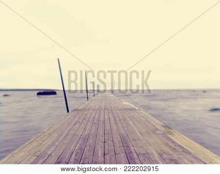 Wet wooden pier in smooth water of sea bay.  Old mole anchored with steel poles into bottom. Iron ladder for passangers and swimmers. Blurred board because long exposure.