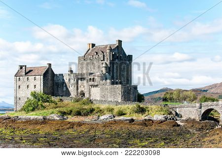 Majestic castle at Eilean Donan on the rock of Loch Alsh with sunny mountains and blue sky on background. Summertime outdoors horizontal image.