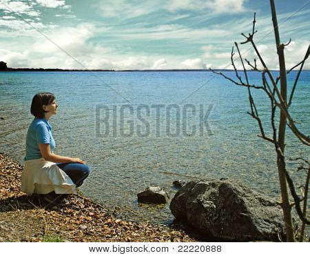 woman on the bank of a lake looks into the distance. unique keyword for this collection is: lake77