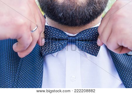 Cute stylish groom in a blue suit, blue necktie and white shirt. Close-up of a gentleman wearing blue Tie straightens his bowtie.