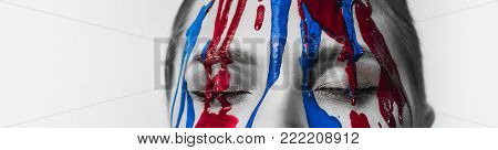 Paint On The Female Face, Close-up. Flows Of Red And Blue Paint On The Face. Artistic Portrait Of A