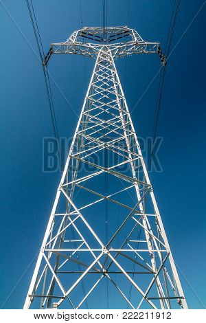 A high voltage power line mast on blue sky background.
