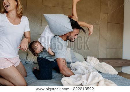 Mother And Son Playing With Pillows In Bedroom