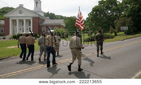 Washington Depot, CT, USA 05.30.2016 veterans day parade participants in uniforms carrying American flag with Bryan Memorial Town Hall in background