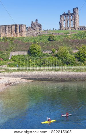 TYNEMOUTH, ENGLAND - MAY 28, 2012: Two kayakers paddle in front of the ruins of Tynemouth Castle and Priory on the coast of North East England.