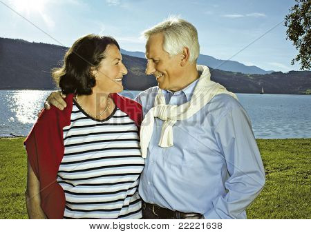attractive married mature couple in the sunset beside a lake. keyword for this collection is