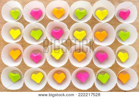 A lot of paper colorful origami heart in round white cupcake molds. Modern bright romantic background. Origami paper hearts geometric volume. Colored paper heart.