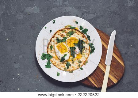 Top view of pitta bread with eggs on it, side view of food dish, vegetarian plate and spices on dark grey background.