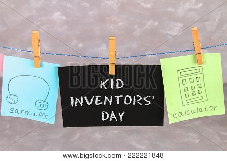 Notes hang on clothes pegs with drawings of children's inventions - popsikl, Earmuffs, calculator on a gray background. Text - Kid Inventors' Day