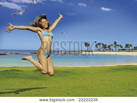 beautiful woman is jumping beside the ocean.