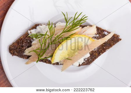 Smoed trout tartine with a slice of lemon and piece of dill.