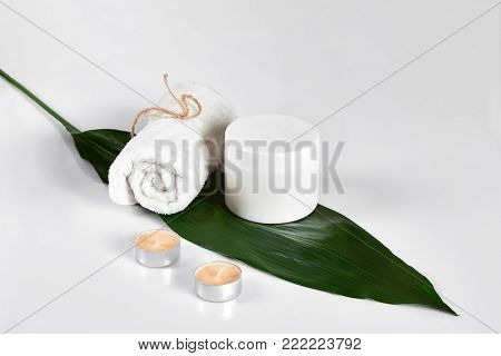 Cosmetic lotion with green leaf and candles. Skin care beauty treatment with jar of body moisturizer. White body lotion with big green leaf on light background.