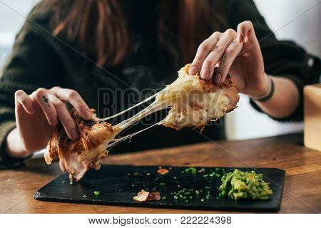 Woman with tattoos on fingers breaks up ready to eat croissant with melted cheese and ham. Tasty and delicious breakfast dish with gooey dairy product. Crunchy and flavorful