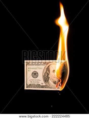 a hundred dollars burn in a fire on a black background .