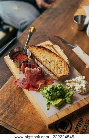 View on beautifully arranged breakfast or brunch plate at cafe or restaurant. Millennial or hipster lunch food with whole wheat bread toast, tomato and avocado spread with added cured ham or jamon