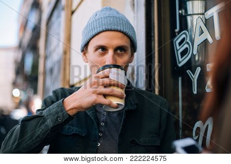 Handsome young millennial or hipster sips on organic tea from infusion bag in take away to go cup, on street outdoors, life on go rush and business, or student before class