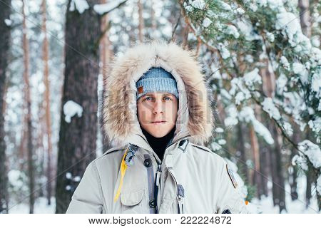 Close up portrait of attractive and handsome caucassian young man with blue eyes and pale skin, in middle of winter forest and snow covered trees,wears warm furry jacket and warms his hands in pockets
