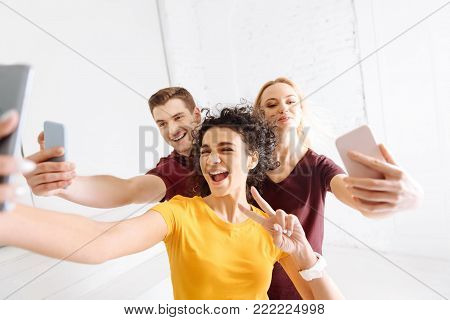 High-spirited. Joyful woman opening mouth and stretching hand while making selfie photo