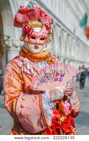 VENICE, ITALY -  FEBRUARY 27, 2014: Carnival of Venice. Beautiful pink carnival mask with fan in St. Mark's Square during celebration of famous carnival.